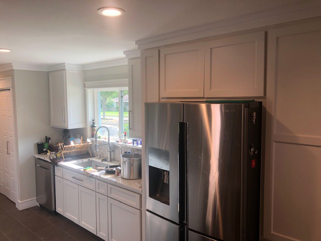 White kitchen cabines around refrigerator