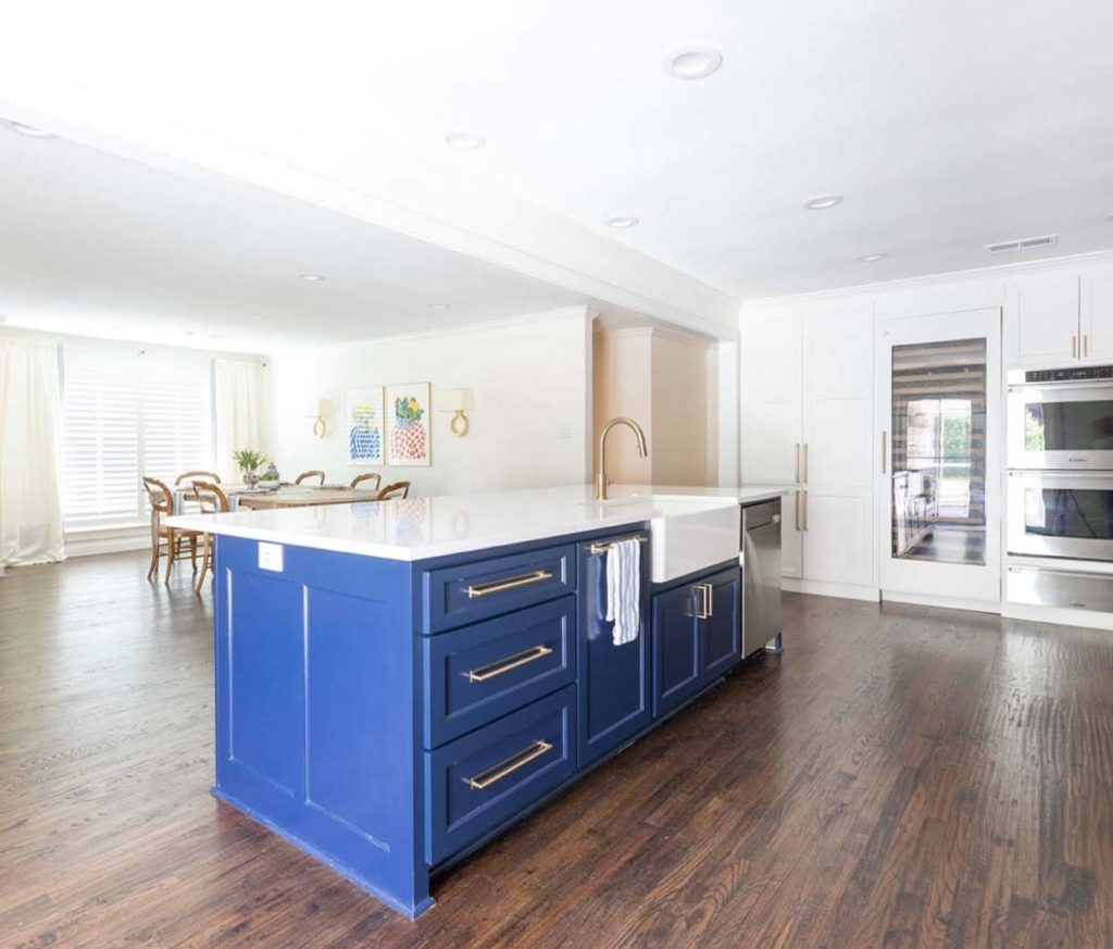 Bold blue kitchen island in white kitchen with wood stained floor